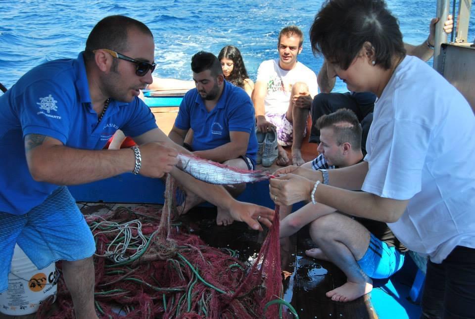 A dx Gianna Saba aiuta il comandante Simone a smagliare un pesce dalla rete